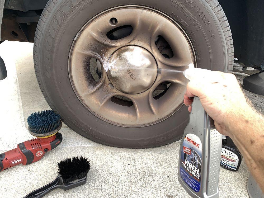 Spraying SONAX Wheel Cleaner Plus onto wheel.
