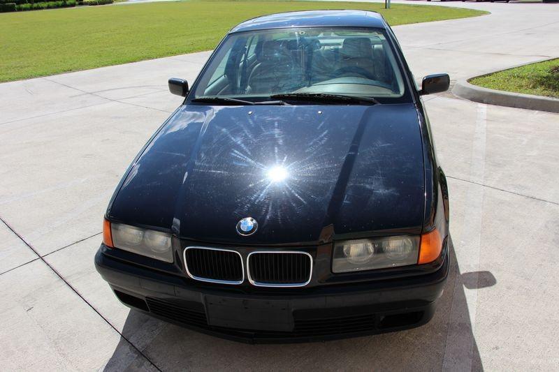 BMW in sun showing severity of paint swirls.