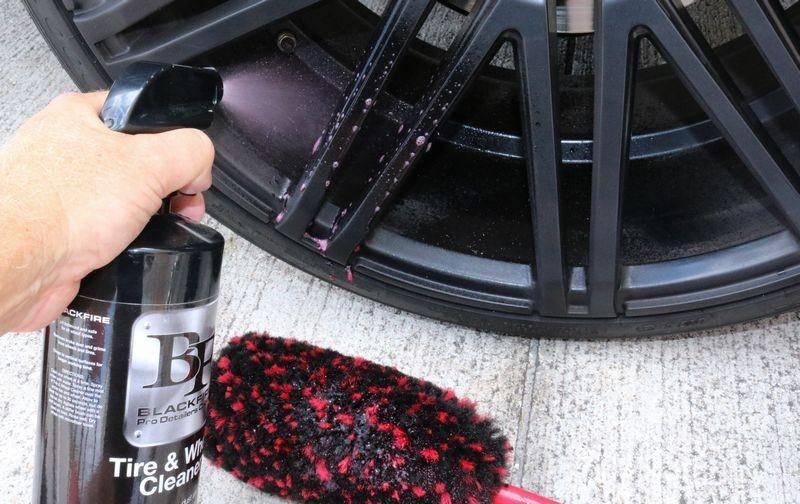 Spraying BLACKFIRE Tire & Wheel Cleaner onto wheel barrels.