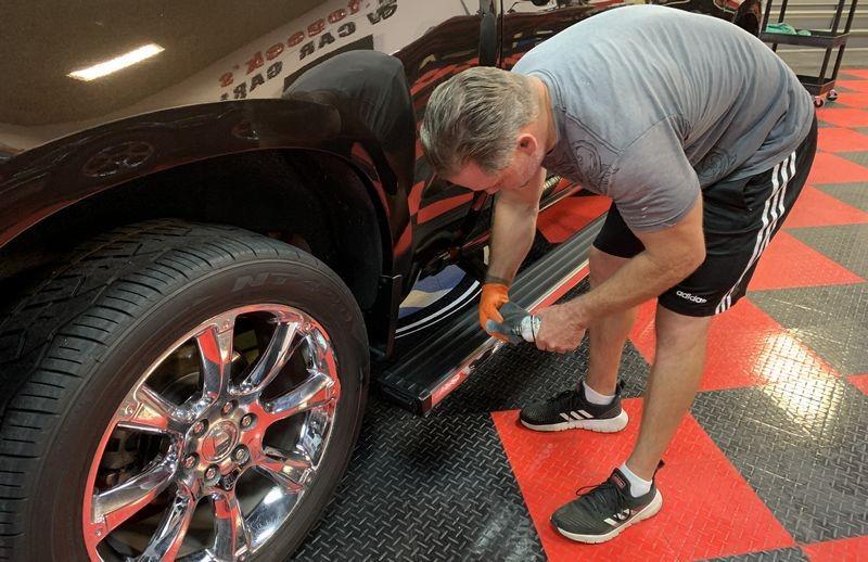Man applying Solution Finish to faded running board trim on truck.