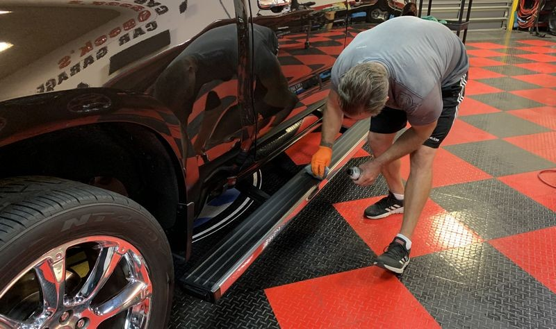 Another shot of a man applying Solution Finish to the running board trim of a truck.