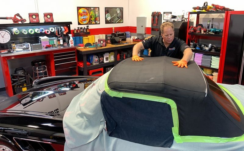 Rubbing RaggTopp Fabric Protectant into convertible top.