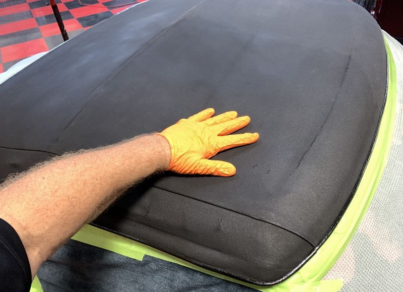 Rubbing protectant into convertible top.