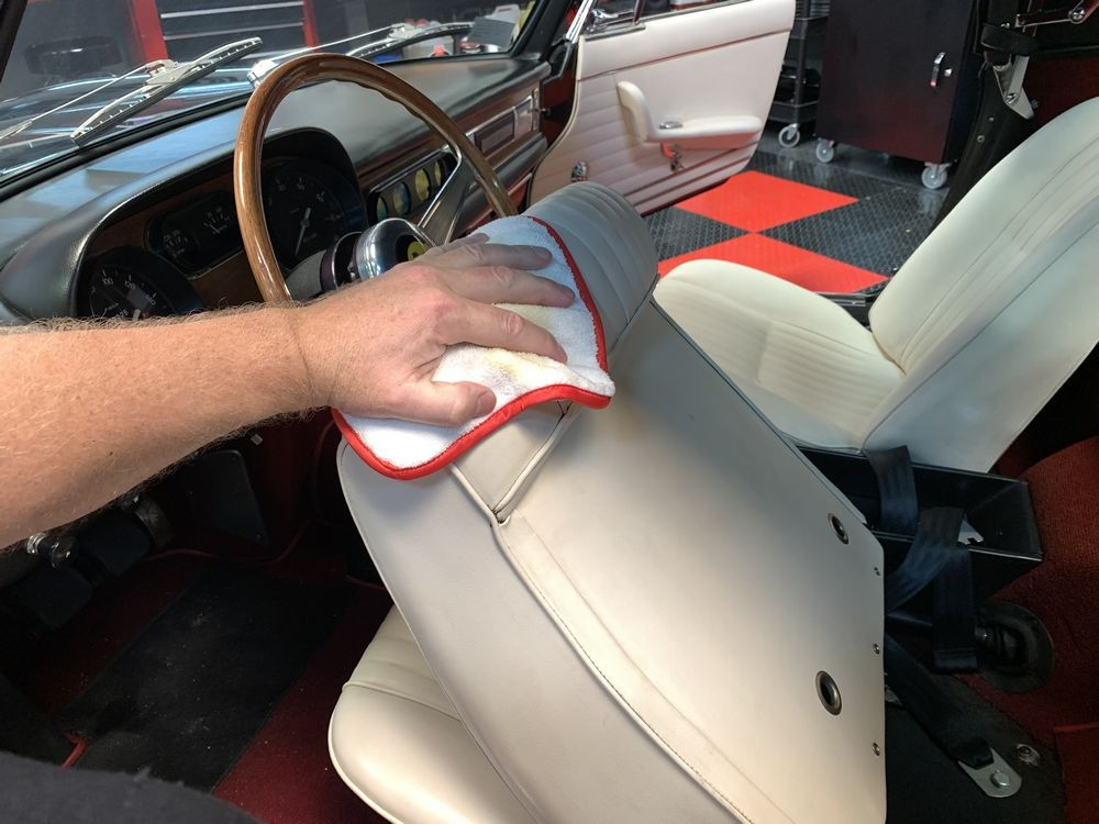 Wiping Leatherique Rejuvenator Oil onto leather seats.