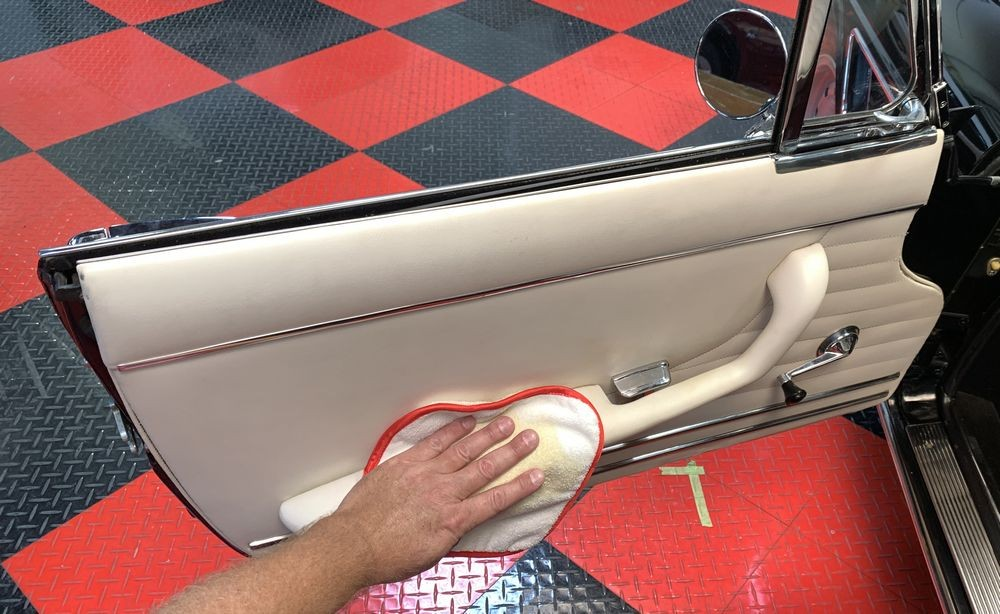 Wiping Leatherique Rejuvenator Oil onto leather surfaces.