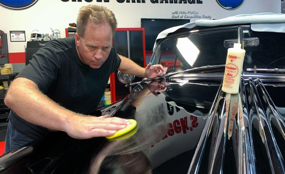 Mike Phillips applying Collinite Wax to car's hood.