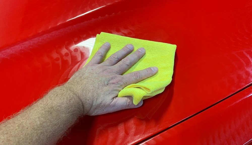 Wiping wax off car.