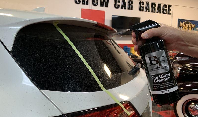 Spraying BLACKFIRE Gel Glass Cleaner onto the dirty glass.