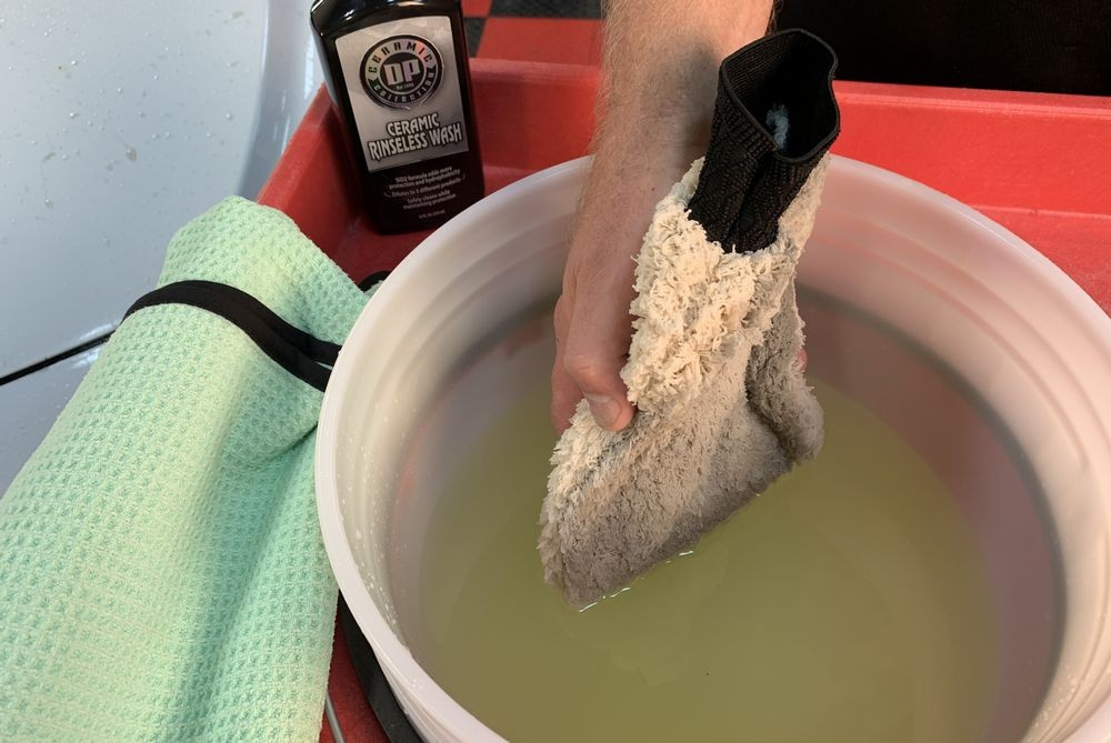 Rinsing mitt in bucket.