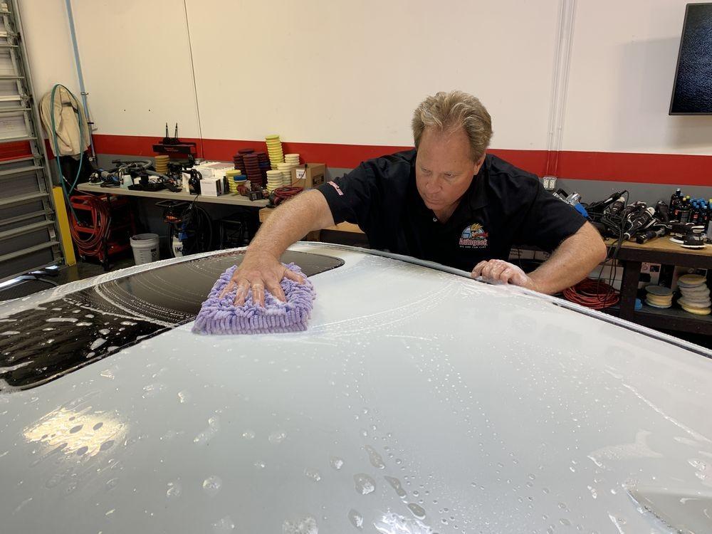 Washing roof of car with purple microfiber mitt.