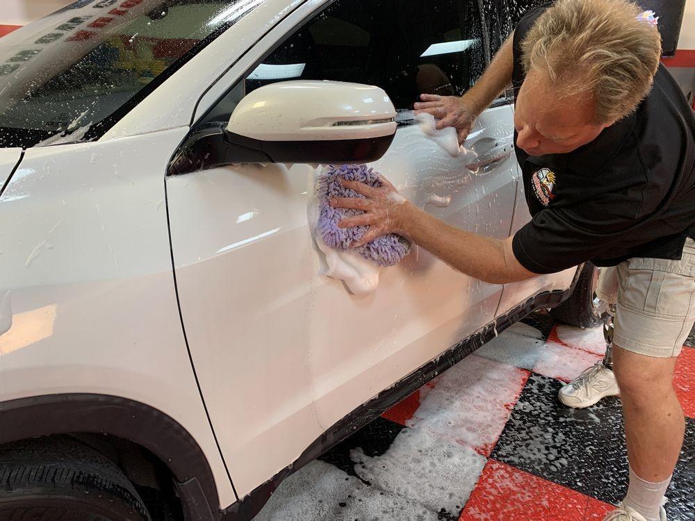 Washing side of car with purple microfiber mitt.
